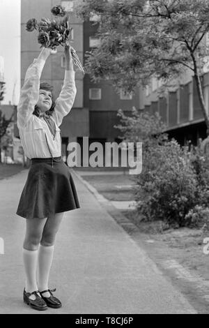 young schoolgirl member of the pioneer movement wearing her necktie and uniform while waving a bunch of flowers in the street 1970s hungary - Stock Photo