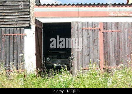 old ruined garage with vintage car through open door - Stock Photo