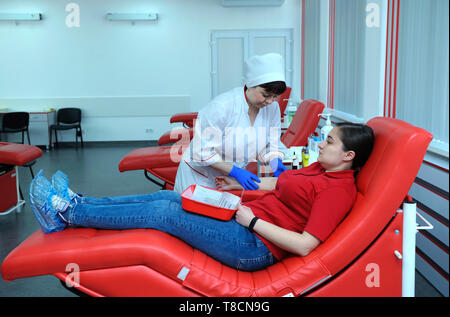 Nurse taking blood from the vain of a donor - hypodermic needle, tubes. The City (municipal) blood transfusion station. April 5, - Stock Photo