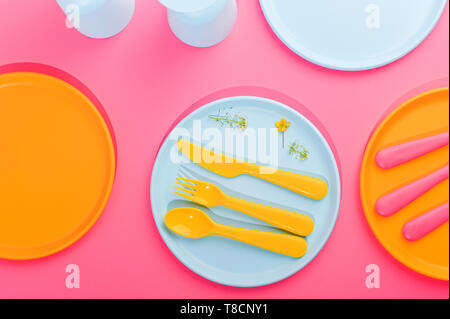 Blue plastic plates and cutlery and glasses. Dishes for a summer picnic. Top view. Pink and yellow color on the photo. Copy space - Stock Photo