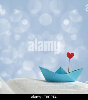 The photo blue paper boat with a red heart on the page of the book, there is space for text. Can be used as a template, romantic greeting card, poster - Stock Photo