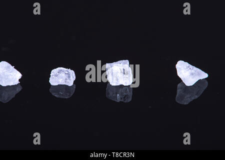 single coarse salt crystals on a black background for health purposes - Stock Photo
