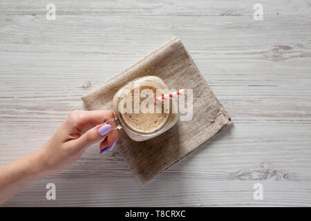 Woman's hand holding a glass jar filled with banana, kiwi, apple smoothie over white wooden surface, top view. - Stock Photo