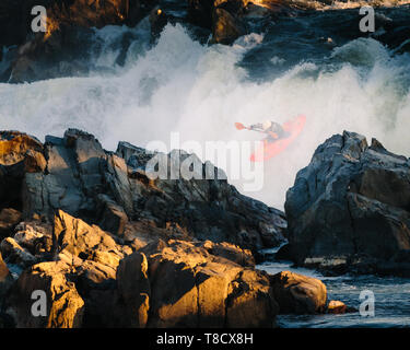 A man in an orange kayak plunges into the rapid at Great Falls Park in Virginia, USA - Stock Photo