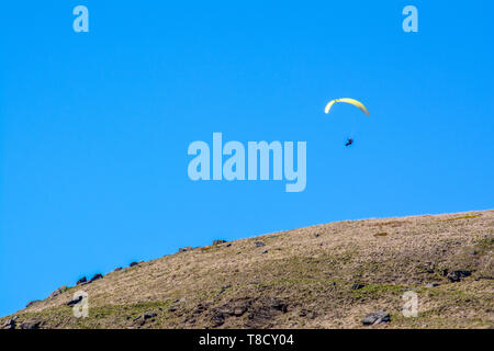 A landscape shot of a hang glider in the air over the hills of yje yorkshire moors. - Stock Photo
