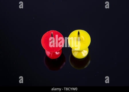two pins in the color red and yellow against black background - Stock Photo