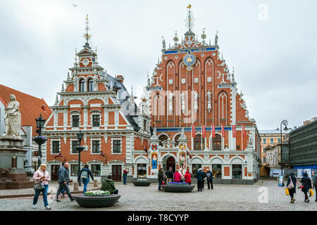 Riga, Latvia, May 02: Tourists walking through the square in front of the building of the House of Blackheads in the old part of Riga, May 02, 2019. - Stock Photo
