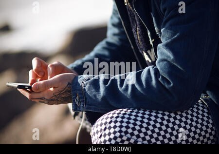 A fashionably dressed man in a denim jacket and plaid pants holds a touch phone in his tattooed hands - Stock Photo