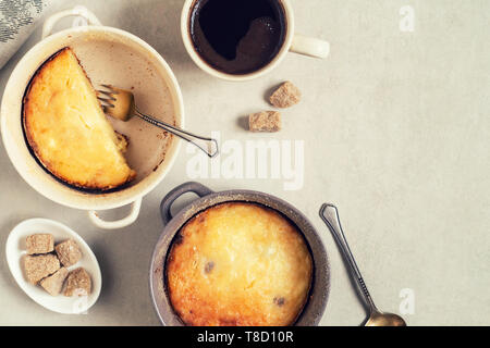 Two pans with cottage cheese casserole and cup of coffee on gray table. Top view - Stock Photo