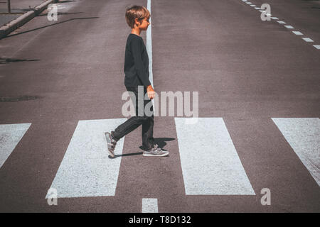 Child crossing the road at pedestrian crossing in the city - Stock Photo