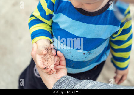 Cute little toddler boy showing mother dirty hands after playing in mud outdoors. Curious child with dirt or soil on palms after discovering world - Stock Photo