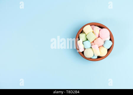 Marshmallows in a round bowl, isolated on blue background. Top view. - Stock Photo