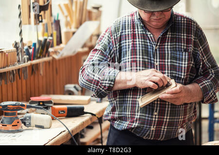 Senior craftsman grinding wooden part with sandpaper grinder machine at carpentry workshop. Mature master polishing details of craft object. DIY home - Stock Photo