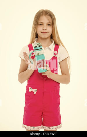 Little girl with plastic bottle isolated on white. Thirsty child in pink jumpsuit hold water bottle. Drinking water for health. Thirst and dehydration. Childhood activity and energy. - Stock Photo