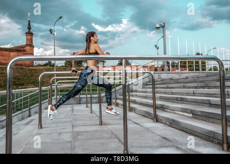 Girl on morning run summer city on background steps of clouds and metal handrails. Fitness sport, active lifestyle of young people. Motivation is - Stock Photo