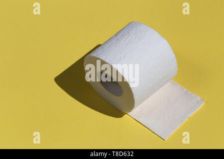 Roll of toilet paper or tissue isolated on yellow background. close up photo. copy space - Stock Photo