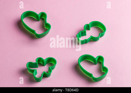 green christmas cookie cutters on the pink table.New year. holiday, useful tool for chef. top view photo - Stock Photo