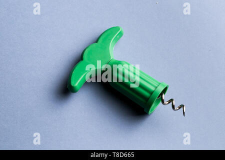 modern green corkscrew isolated on blue background, top view photo. close up shot - Stock Photo