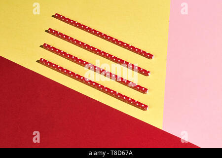 four plastic ecological vintage straws isolated on the yellow, pink, red background , top view photo