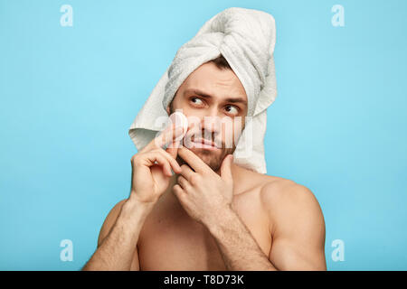 funny puzzled man cleaning his face with cotton swabs. close up photo. spa procedure concept - Stock Photo