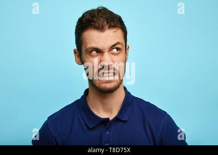 nervous annoyed man in T-shirt snapping, looking at copy space, ,clenching his teeth, studio shot.close up portrait - Stock Photo