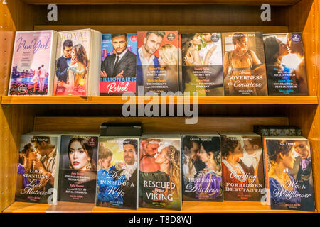 A selection of Mills & Boon paperback romantic novels and historical romances displayed for sale in a bookshop. - Stock Photo