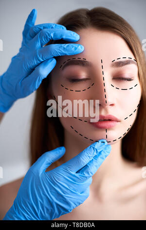 Beautiful young woman with perforation lines on her face before plastic surgery operation. Beautician hands in gloves touching woman face. Puncture - Stock Photo