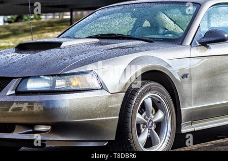 A 2001 Ford Mustang GT Coupe glistening in the sun after a summer storm. Glistening water droplets cover the body of the sports car. - Stock Photo