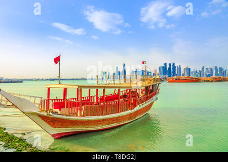 Perspective view of a traditional wooden dhow in foreground with seafront of Doha Bay and skyscrapers of West Bay skyline on background. Capital of - Stock Photo