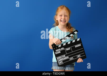 Cute little girl with clapper board on color background - Stock Photo