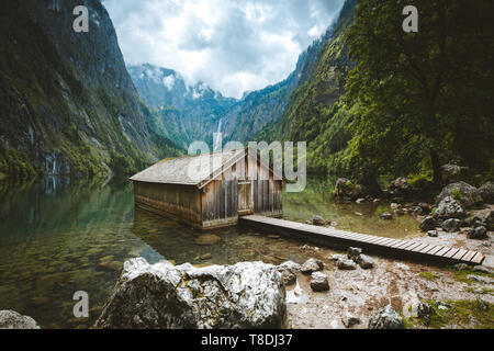 Panoramic view traditional old wooden boat house at scenic Lake Obersee on a beautiful day with blue sky and clouds in summer, Bavaria, Germany - Stock Photo