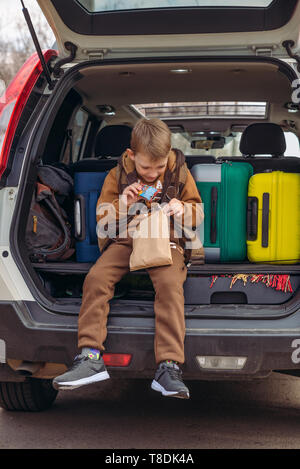 little kid looking into paper bag with candies sitting in car trunk full of bags. - Stock Photo