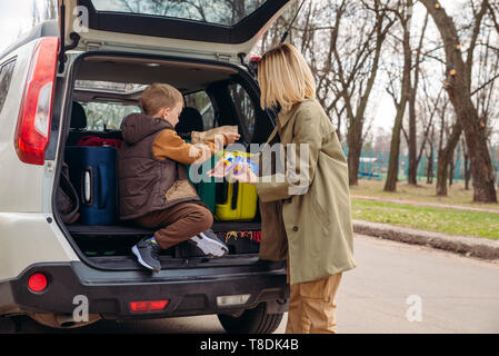 little kid sitting with mother in car trunk full of luggage eating chocolate candies. car travel concept - Stock Photo