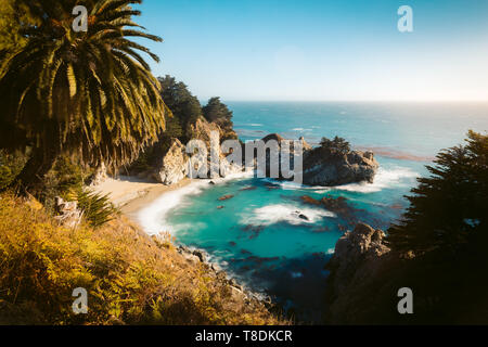 Famous McWay Falls in golden evening light at sunset on a beautiful sunny day with in summer, Julia Pfeiffer Burns Stae Park, Big Sur, California, USA - Stock Photo