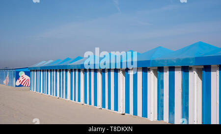 Blue and white striped beach huts on the sand on the sea front at Malo-Les-Bains beach in Dunkirk, France - Stock Photo