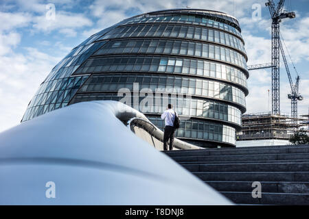 Man on Mobile phone standing on the steps of City Hall London - Stock Photo