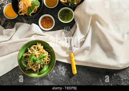 Bowl of delicious pasta with pesto sauce on table - Stock Photo