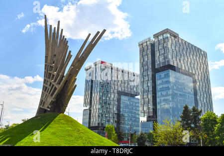 Abstract statue in front of the City Gate Towers, two class A office buildings located in Press Square of Bucharest, capital of Romania. - Stock Photo