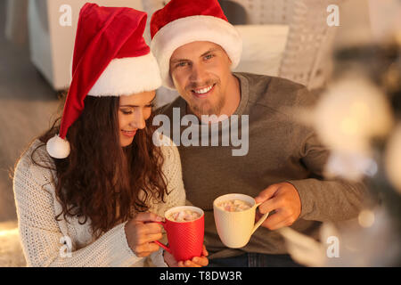 Cute young couple in Santa hats drinking hot chocolate while celebrating Christmas at home - Stock Photo