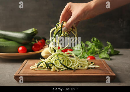 Woman holding zucchini noodles over wooden board in kitchen - Stock Photo