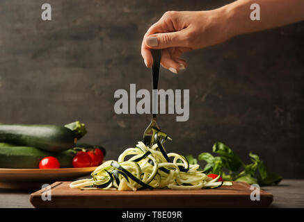 Woman holding fork with zucchini noodles over wooden board in kitchen - Stock Photo