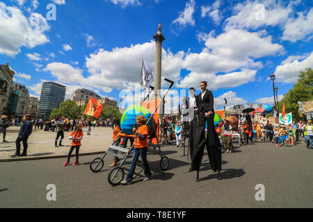 """London, UK. 12th May, 2019. Protesters on stilts march with thousands of parents, accompanied with children  and their families  who marched  in central London to demand urgent action to tackle climate change after British health secretary Matt Hancock named """"dirty air"""" as the """"largest environmental risk to public health in the UK"""" and warned of a growing national health emergency triggered by the """"slow and deadly poison"""" of air pollution. Credit: amer ghazzal/Alamy Live News - Stock Photo"""