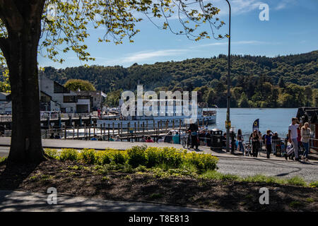Bowness Bay, Lake Wndermere, Cumbria, United Kingdom. 13th May, 2019. MV Swan the Lake Windermere Ferry Leaving pier at Bowness-on-Windermere watched by visitors on the promenade in bright sunshine Credit: Photographing_North/Alamy Live News - Stock Photo