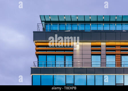 Modern high-rise office building with a glass facade at overcast, background. - Stock Photo
