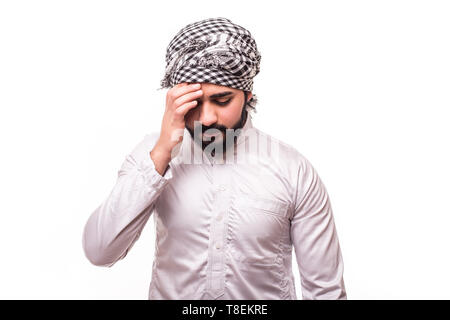 Young arab man wear traditional abaya clothes suffering from head ache on white background - Stock Photo