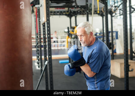 Senior male boxer ready to fight. Senior boxer in gloves boxing in gym. - Stock Photo