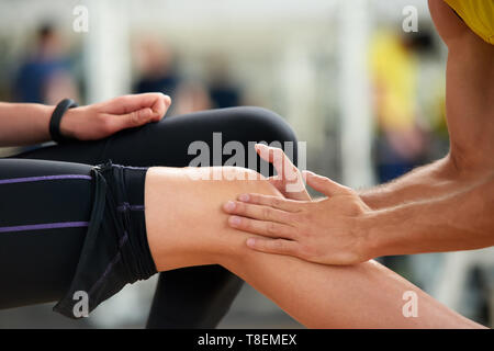 Woman feeling ache in knee after workout. Young woman suffering from knee injury while exercising at sport club. Massage after workout. - Stock Photo