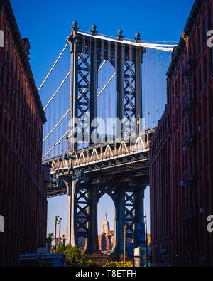Manhattan bridge seen from a narrow alley enclosed by two brick buildings on a sunny day in summer - Stock Photo