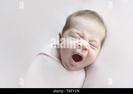 Newborn baby girl yawning lying in a pink blancket - Stock Photo