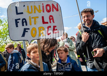 Two boys are seen holding a placard with their family during the march. Thousands of people gathered at the North Station in Brussels during a march for the climate and social justice for all. With the imminent European elections, several organizations launched this demonstration to unite the climate movement, for social justice and against racism, to uphold their fundamental rights. - Stock Photo